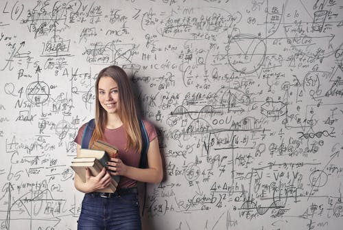 A student holding books, standing in front of a white board