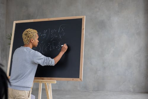 A student writing on a blackboard