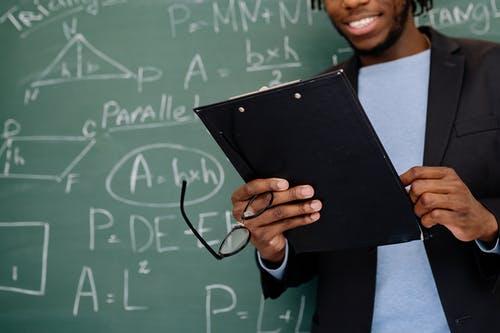 A teacher in front of a blackboard